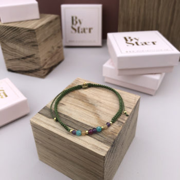 billede af ellie armbånd i grønt på træklods med opsatte smykkeæsker i baggrunden